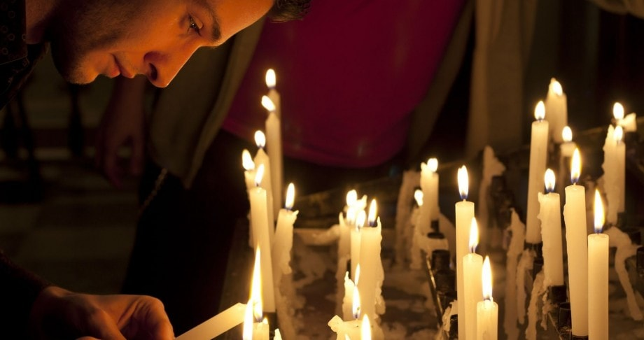 Person lighting a candle for prayer